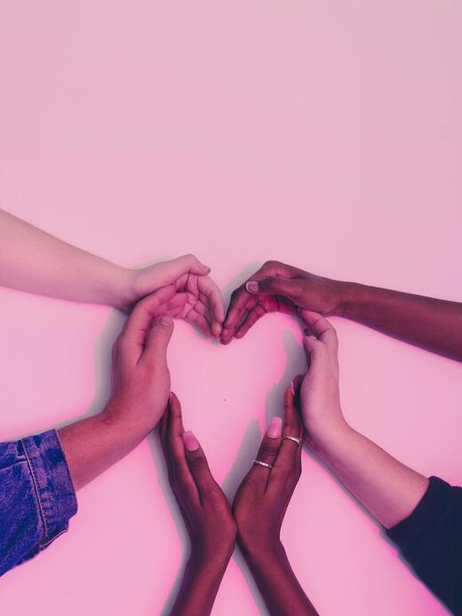 Hands of all races creating a heart